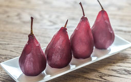 Merlot-poached pears on the plate. On the wooden table Stock Image