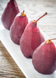 Merlot-poschierte Birnen auf der Platte Stockfoto