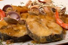 Merluza a la sidra. Hake with seafood in cider sauce, Spanish recipe Stock Photos