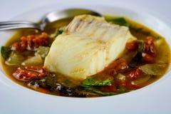 Merluzzo con i pomodori seccati al sole, i verdi e la minestra dell'aglio Fotografia Stock Libera da Diritti