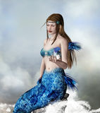 Mermaid. Beautiful mermaid on a rock with a little fish - artistic fantasy portrait Royalty Free Stock Photo