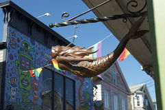 Mermaid and Aliens. Picture taken in Provincetown, down Cape Cod, MA. In front is a Mermaid that hangs in front of a shop and in the back is a building with stock images