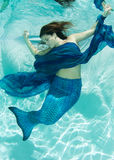 Mermaid in blue water wearing blue Stock Photography