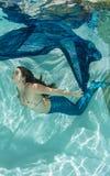 Mermaid in blue water wearing blue Stock Image