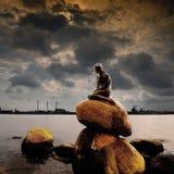 Mermaid cloudy sky. Famous little mermaid statue in harbor of Copenhagen Denmark, with cloudy sky stock photos