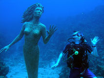 Mermaid and diver. A diver mimics a beautiful mermaid statue, Grand Cayman Royalty Free Stock Photos