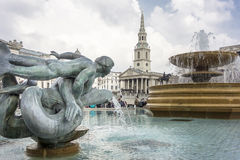 Mermaid and Dolphin Statue and fountain, Trafalgar Square, London. Statue of a mermaid with dolphins in the fountains of Trafalgar Square, with a statue of King Stock Images