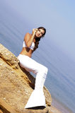 Mermaid. A girl dressed as a mermaid sitting on a rock against the sea Stock Photos