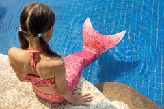 Mermaid girl with pink tail on rock at poolside put feet in water. Top view. Fun, vacation concept. Text space stock photo