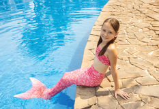 Mermaid girl with pink tail on rock at poolside. Put feet in water. Top view. Fun, vacation concept. Text space Stock Photos
