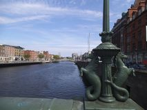 A mermaid horse statue on a bridge in Dublin. In the background is a river with bildings shown stock image