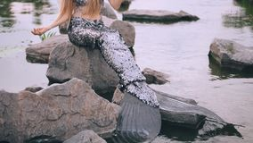 Mermaid with long blond hair, siren costume with silver tail and delightful pearl diadem sitting on stone in the middle. Of the lake, enjoys silence, slowly stock footage