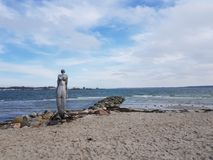 Mermaid. Statue at the beach of Eckernförde with the German navy in the Back Stock Image