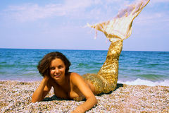 Mermaid. The photo shows a young woman dressed as a mermaid. her golden tail Royalty Free Stock Photography