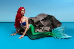 Mermaid with red hair resting near stone. On blue background royalty free stock images