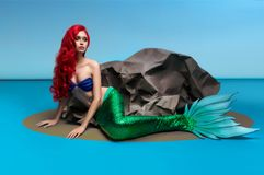 Mermaid with red hair resting near stone. On blue background royalty free stock image