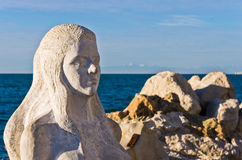 Mermaid sculpture carved out of the stone rocks at Piran harbor, Istria Stock Photography