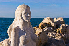 Mermaid sculpture carved out of the stone rocks at Piran harbor, Istria Royalty Free Stock Photo
