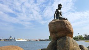 The Mermaid, sculpture in Copenhagen, Denmark. The Mermaid sculpture, landmark of Copenhagen, in the background the Danish royal yacht Dannebrog, Copenhagen stock video footage