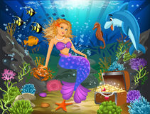 Mermaid sitting on a rock underwater surrounded by fish Stock Photos