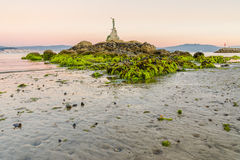 Mermaid statue with low tide in Cangas do Morrazo. A mermaid statue with low tide in a beach of Cangas do Morrazo, with sunset light background Royalty Free Stock Photos