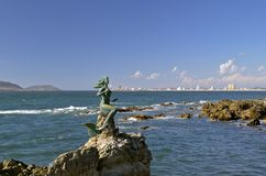 Mermaid statue in Mazatlan. Mermaid statue off the coast of Mazatlan on with the Malecon walkway and city in the background Stock Image