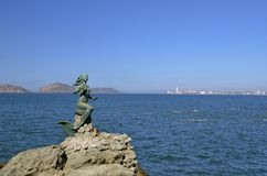 Mermaid statue in Mazatlan. Mermaid statue off the coast of Mazatlan with the city skyline and the Malecon byway in the background Stock Image