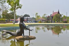 The Mermaid Statue in the water and community background royalty free stock photo