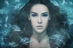 Mermaid. Surreal mermaid woman portrait surrounded by fishes, composite photo Royalty Free Stock Photo