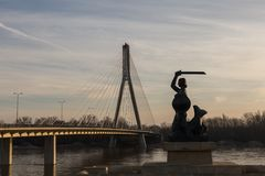 Mermaid and Swietokrzyski bridge in Warsaw. Mermaid Syrenka and Swietokrzyski bridge over Vistula river in Warsaw, Poland stock photos