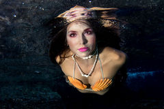 Mermaid swimming underwater in the deep blue sea. Black hair Mermaid swimming underwater in the deep blue sea and looking at you royalty free stock photography