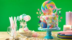 Mermaid theme candyland cake with glitter tails, shells and sea creatures. Mermaid theme candyland cake with colorful glitter tails, shells and sea creatures royalty free stock image