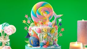 Mermaid theme candyland cake with glitter tails, shells and sea creatures. Mermaid theme candyland cake with colorful glitter tails, shells and sea creatures stock image