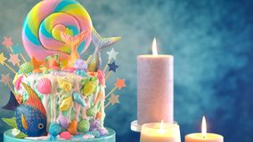 Mermaid theme candyland cake with glitter tails, shells and sea creatures. Mermaid theme candyland cake with colorful glitter tails, shells and sea creatures royalty free stock photo