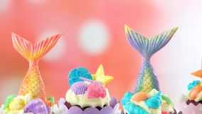 Mermaid theme cupcakes with colorful glitter tails, shells and sea creatures. Mermaid theme cupcakes with colorful glitter tails, shells and sea creatures stock image