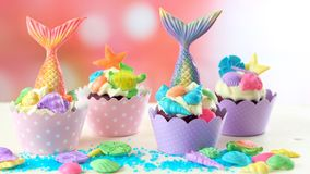Mermaid theme cupcakes with colorful glitter tails, shells and sea creatures. Mermaid theme cupcakes with colorful glitter tails, shells and sea creatures stock photography