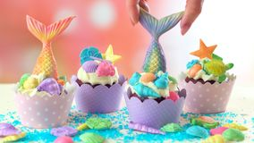 Mermaid theme cupcakes with colorful glitter tails, shells and sea creatures. Mermaid theme cupcakes with colorful glitter tails, shells and sea creatures royalty free stock image