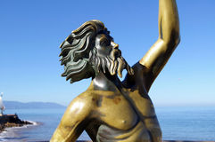 Merman Statue. Tarnished green merman statue of Poseidon or king Neptune in Mexico showing chest and head against clear blue sky royalty free stock images