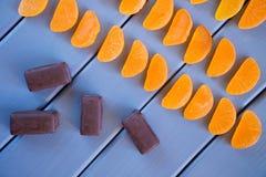 Mermelada anaranjada bajo la forma de rebanadas de la mandarina y caramelos de chocolate en una tabla hecha de tableros de madera foto de archivo