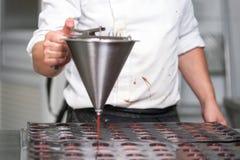 Mermelada de colada de la fresa del chef de reposter?a, trabajando en la cocina de la tienda de pasteles imagen de archivo libre de regalías
