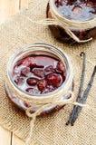 Mermelada de fresa en un tarro de cristal en harpillera con las vainas de la vainilla Imágenes de archivo libres de regalías