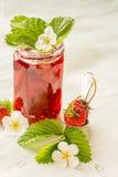 Mermelada de fresa en un vidrio adornado con las hojas Imagen de archivo libre de regalías