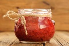 Mermelada de fresa hecha en casa en el tarro de cristal con hempstring en el na del papel Fotos de archivo libres de regalías