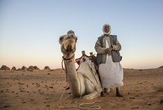 Man with his camel in a desert in Sudan Stock Image