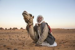 Man with his camel in a desert in Sudan Royalty Free Stock Photos