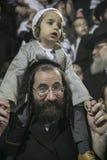 MERON,以色列26日2016年:一个未认出的可爱的Hasidic男孩在他的父亲的肩膀高兴,当佩带他的父亲时 免版税图库摄影
