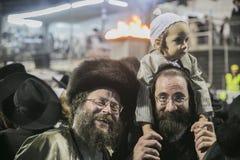 MERON,以色列26日2016年:一个未认出的可爱的Hasidic男孩在他的父亲的肩膀高兴,当佩带他的父亲时 库存照片