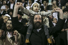 MERON,ISRAEL- MAY 26, 2016: An unidentified adorable Hasidic boy rejoices on his fathers' shoulders while wearing his fathers. An unidentified adorable Hasidic Royalty Free Stock Photography