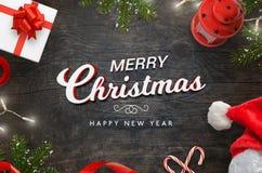 Merr jul smsar på den svarta trätabellen surrrounded med julgranen, gåvan, sötsaker, ljus Royaltyfria Bilder