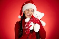 Merriment. Joyful girl in Santa cap with white teddy bear looking at camera Stock Photography